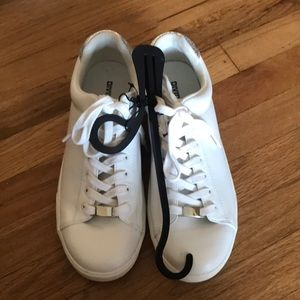 H&M white sneakers with silver trim on the back.
